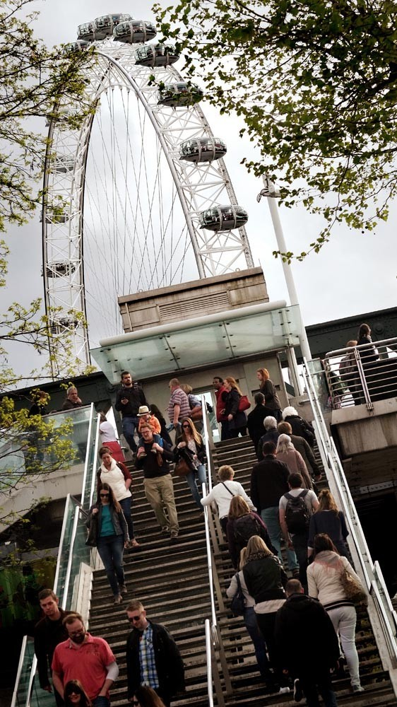 view of the London eye from the steps on the south bank